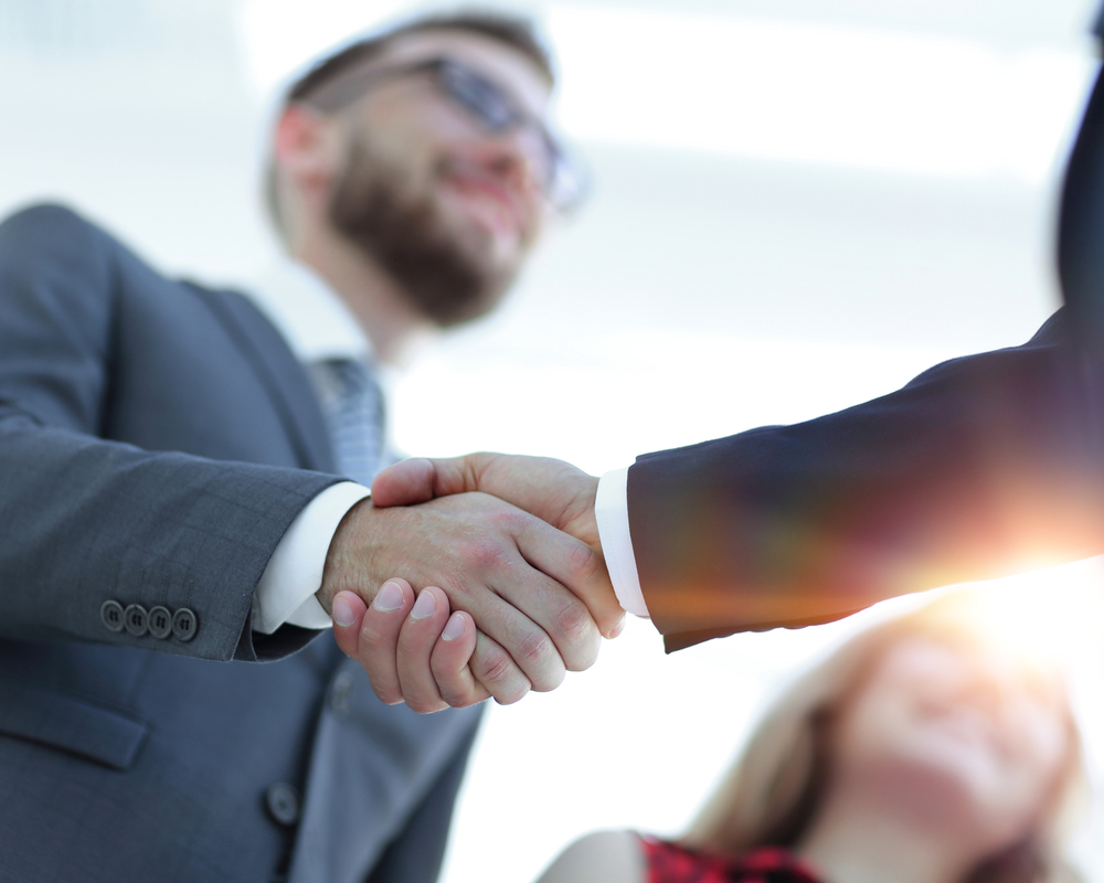Image of lawyer shaking hands after a successful business sale